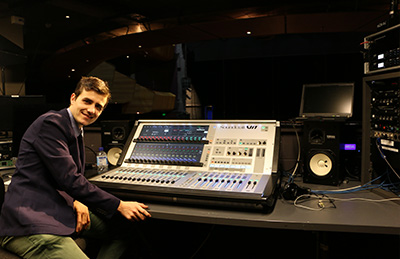 BFA Technical theatre student next to sound mixing board